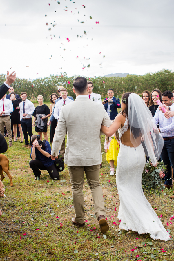 bride and groom are showered by rose petals in stellenbosch
